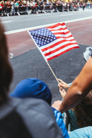 Photo for Close up view of american flag in childs hands during parade on street in new york, usa - Royalty Free Image
