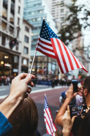 Photo for Partial view of man holding american flag during parade on street in new york, usa - Royalty Free Image