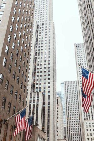 Foto de Vista de ángulo bajo de rascacielos y banderas americanas en la calle de la ciudad de nueva york, Estados Unidos - Imagen libre de derechos