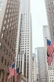 """Постер, картина, фотообои """"низким углом зрения небоскребов и американские флаги на улице Нью-Йорк, США"""""""