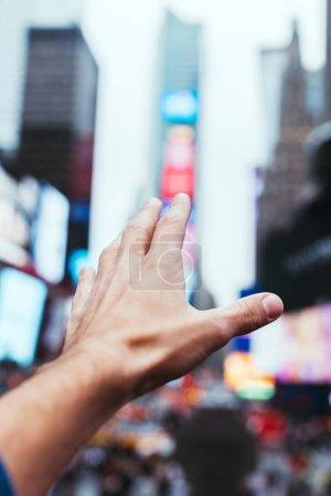 Foto de Vista parcial de la mano masculina y borrosa calle de la ciudad de nueva york sobre fondo - Imagen libre de derechos