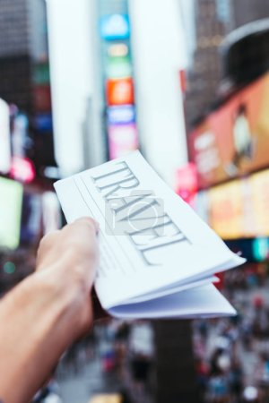 partial view of man holding travel newspaper with blurry new york city street view on background