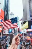 """Постер, картина, фотообои """"частичное представление о мужчина держит американский флаг на улице Нью-Йорка"""""""