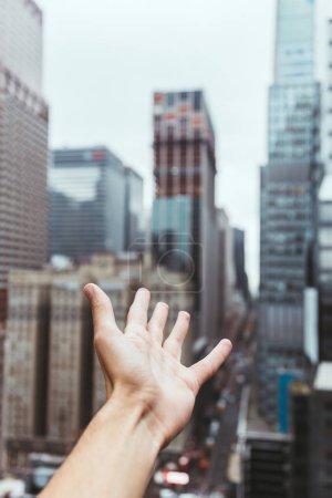 Photo pour Vue partielle de la main masculine et floue vue de new york city sur fond - image libre de droit