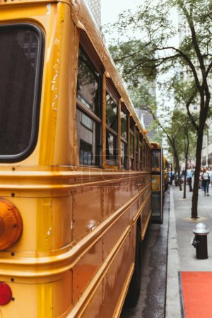 urban scene of parked yellow school buses on street in new york, usa