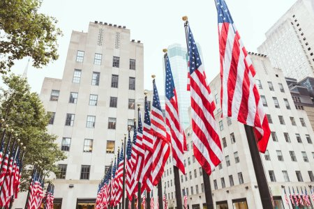 low angle view of american flags and buildings, new york, usa