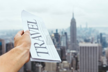Photo for Partial view of man holding travel newspaper with blurry new york city view on background - Royalty Free Image