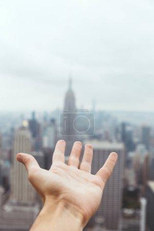 Photo pour Vue partielle de la main masculine et vue floue de la ville de New York en arrière-plan - image libre de droit