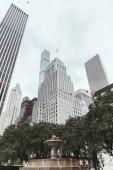 """Постер, картина, фотообои """"низкий угол зрения небоскребов, деревьев и городской фонтан в Нью-Йорке, США"""""""