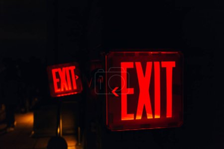 close up view of red exit sign on black backdrop