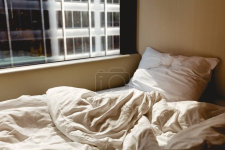Photo for Close up view of empty bed near window in hotel room - Royalty Free Image