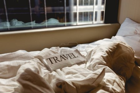 Photo for Close up view of travel newspaper on bed in hotel room - Royalty Free Image