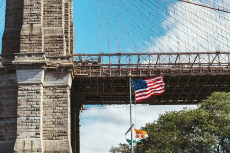 close up view of brooklyn bridge and american flag in new york, usa