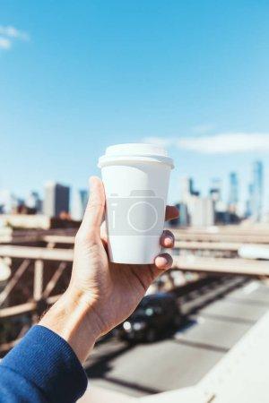 Photo pour Vue partielle de l'homme tenue jetable tasse de café avec floue new york city à fond - image libre de droit