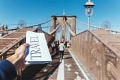 """Постер, картина, фотообои """"частичное представление о мужчина держит газету путешествия с размытыми видом на мост Нью-Йорк на фоне"""""""