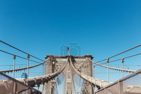 brooklyn bridge with american flag on clear blue sky background, new york, usa