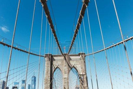 Photo pour Brooklyn pont avec drapeau américain sur ciel bleu clair et manhattan sur fond, New York, États-Unis - image libre de droit