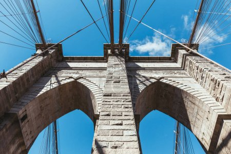 Photo for Bottom view of brooklyn bridge against blue cloudy sky background in new york, usa - Royalty Free Image
