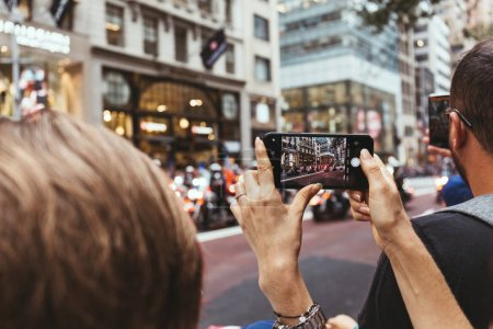 Photo for NEW YORK, USA - OCTOBER 8, 2018: woman taking picture of city parade on street in new york, usa - Royalty Free Image