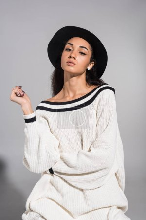 Photo for Attractive african american young woman in stylish white clothes and hat looking at camera on white - Royalty Free Image