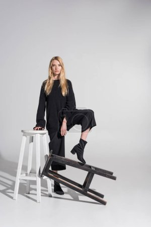 Photo for Beautiful caucasian blonde woman in black clothes standing and putting leg on chair on white - Royalty Free Image