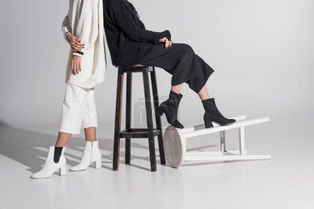 Photo pour Image recadrée de multiculturelle des femmes dans des vêtements noirs et blancs avec des chaises sur blanc - image libre de droit