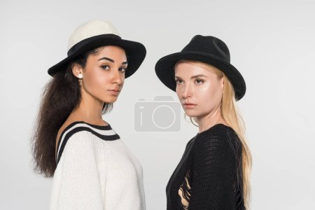 Photo pour Portrait de belles femmes multiethniques en vêtements noirs et blancs et chapeaux isolé sur blanc - image libre de droit