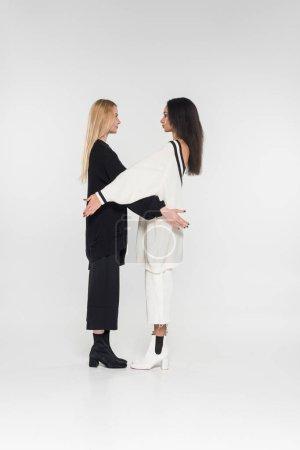 Photo pour Belles femmes multiculturelles en vêtements noirs et blancs permanent et regardant les uns les autres sur blanc - image libre de droit