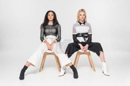 Photo pour Jolies femmes multiethniques dans des vêtements noirs et blancs qui posent sur des chaises et regardant la caméra isolé sur blanc - image libre de droit