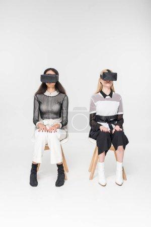 Photo pour Multiculturelle des femmes dans les casques de réalité virtuelle assis sur des chaises isolés sur blanc - image libre de droit