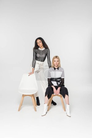 Photo for Attractive multiethnic women in fashionable black and white clothes sitting on chairs isolated on white - Royalty Free Image