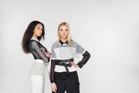 Photo pour Jolies femmes multiethniques dans des vêtements noirs et blancs posant et en regardant la caméra isolé sur blanc - image libre de droit