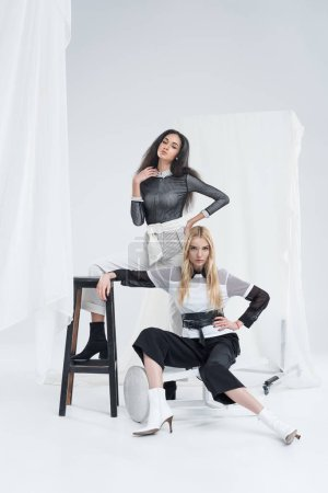 Photo pour Jolies femmes multiculturelles dans les vêtements noirs et blancs qui posent sur des chaises près de tulle blanc - image libre de droit