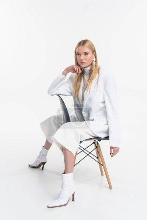 attraktive kaukasische Blondine in modischer weißer Kleidung sitzt auf einem Stuhl und schaut isoliert auf weißem Grund weg