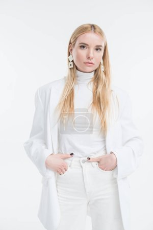 attractive caucasian blonde woman in fashionable white clothes and earrings looking at camera isolated on white