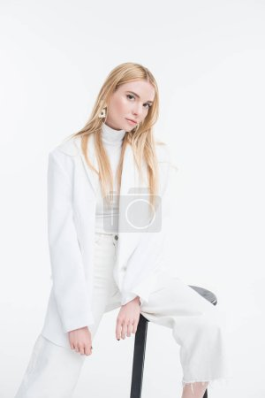 Photo for Attractive caucasian blonde woman in fashionable white sweater and jacket sitting on chair and looking at camera isolated on white - Royalty Free Image