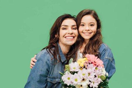 Photo pour Sourire de mère et fille avec fleurs en regardant la caméra isolée sur vert - image libre de droit