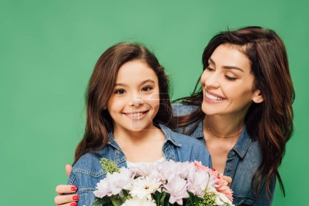 happy mother embracing adorable daughter with flower bouquet isolated on green