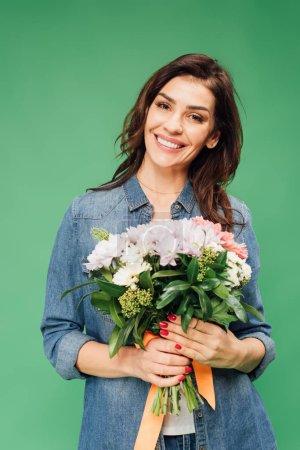 Photo pour Femme séduisante souriante tenant le bouquet de fleurs et regardant la caméra isolée sur vert - image libre de droit
