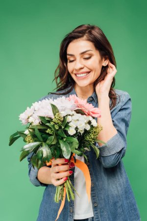 Photo for Beautiful smiling woman touching hair and holding flower bouquet isolated on green - Royalty Free Image