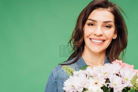 retrato de mujer sonriente sosteniendo ramo de flores aislado en verde