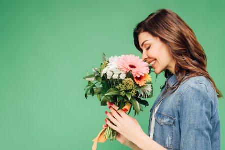 Photo pour Femme souriante tenant et reniflant bouquet de fleurs isolé sur vert - image libre de droit