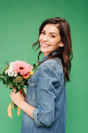Photo pour Jolie femme tenant le bouquet de fleurs et regardant la caméra isolée sur vert - image libre de droit