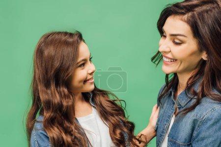 Photo pour Portrait de l'heureuse mère et fille souriant et en regardant l'autre isolé sur vert - image libre de droit