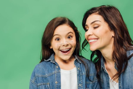 portrait of smiling mother and surprised daughter isolated on green