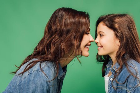 Photo for Happy mother and daughter looking at each other isolated on green - Royalty Free Image