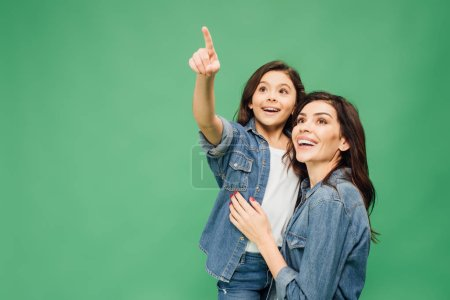 Photo for Excited daughter pointing with finger while happy mother looking up isolated on green - Royalty Free Image