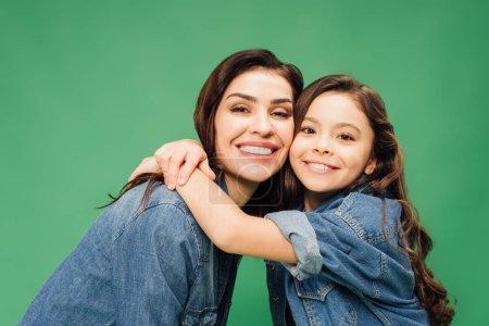 Photo pour Mère heureuse et fille embrassant et regardant la caméra isolée sur vert - image libre de droit