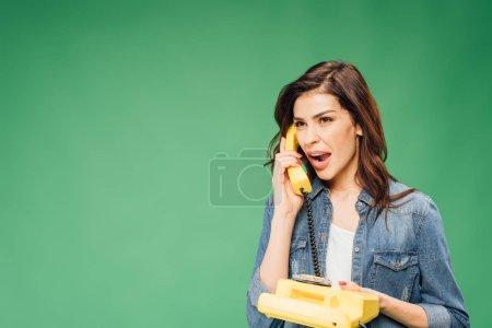 Photo pour Belle femme surprise téléphone vintage isolé sur vert - image libre de droit