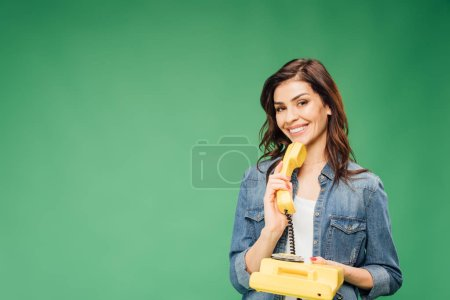 Photo for Beautiful woman holding vintage telephone isolated on green - Royalty Free Image